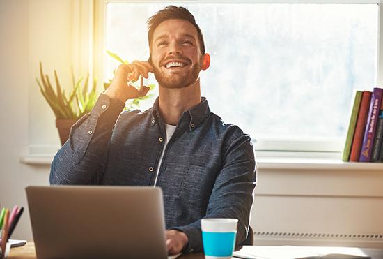 Mann sitzt am Laptop und telefoniert