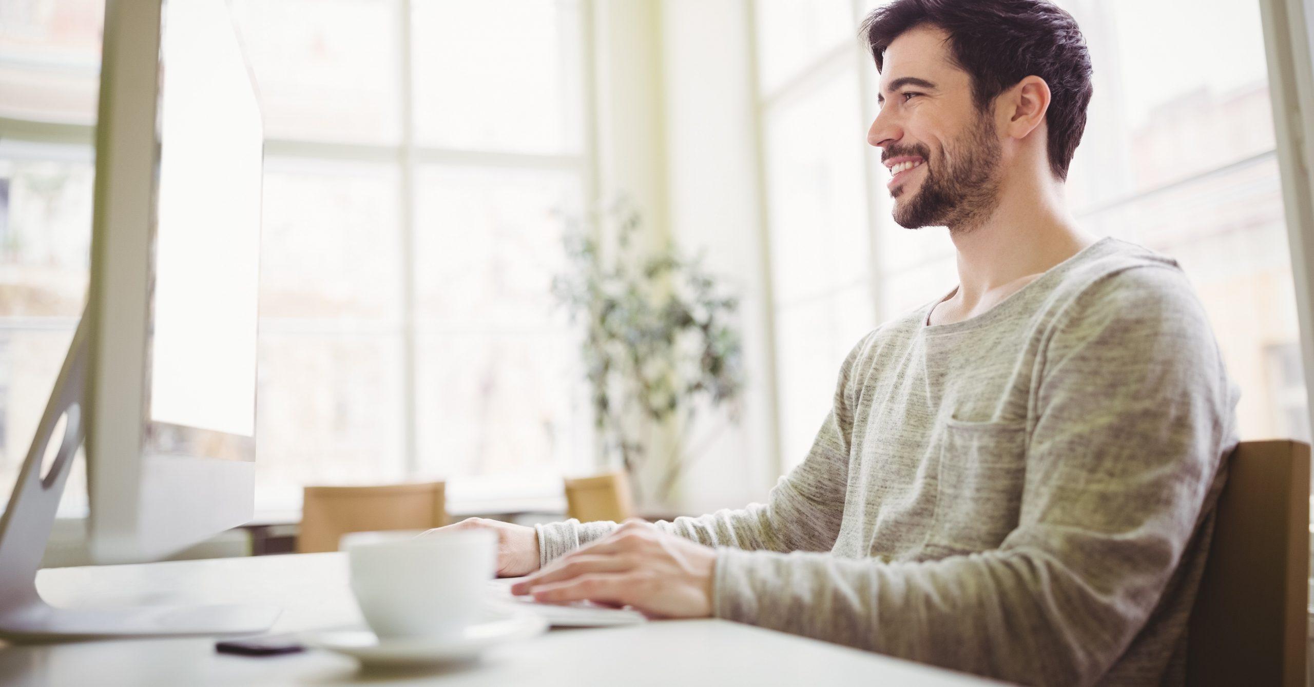 Businessmann sitzt lächelnd am Arbeitsplatz im Büro