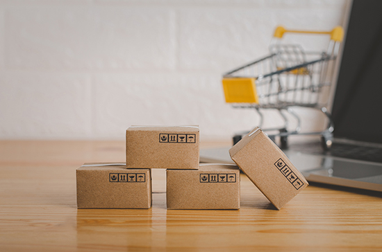 Brown paper boxs with laptop on wood table in office background.Easy shopping with finger tips for consumers.Online shopping and delivery service concept.