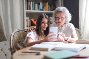 Seniorin und Enkelkind sitzen am Tisch und schauen auf Smartphone. Es soll die Technikaffinität von Senioren darstellen.